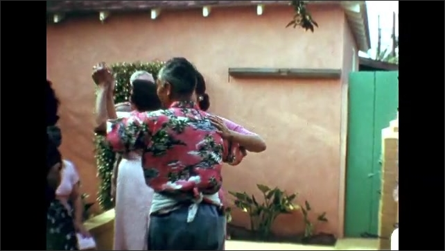 1960s: Man and woman dance on outdoor patio. Three couples dance on outdoor patio. Man stops dancing and tends to food cooking on grill.