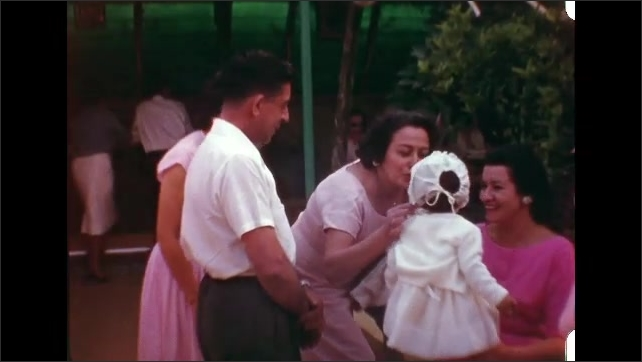 1960s: Woman sits with little girl on her lap as people sit around them, talking. Woman kisses little girl. People talk to little girl.