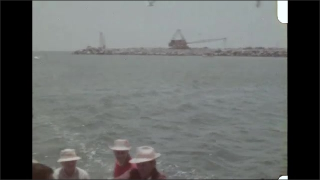 1960s LOS ANGELES: Man on fishing boat holds up a balance scale with a fish on each side and tries to find the biggest. Seagulls fly behind the fishing boat.