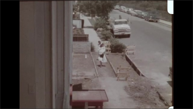 1960s LOS ANGELES: Construction worker enters Porta-Potty outside motel building site. Building site of motel under construction. Street scene of traffic and pedestrians by motel.