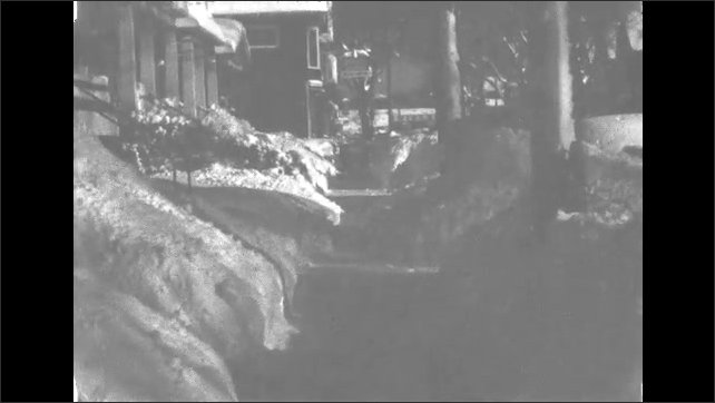 1940s Buffalo: People walk along snowy city sidewalks. Icicles hang off roof of cabin. Snow piles along suburban sidewalks. Snow piles in front of house.