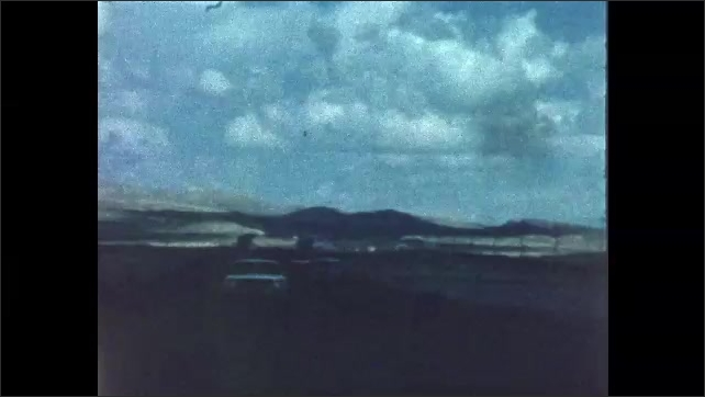 1970s: Car drives down highway. Clouds in sky. Hills on horizon.