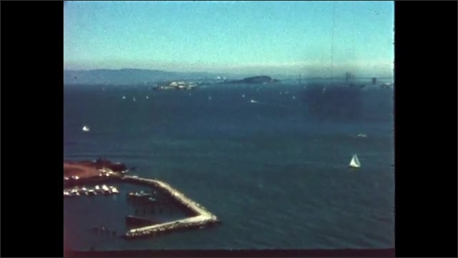 1970s: San Francisco Bay. Boy standing on cliff looking at bay. Boats in bay.