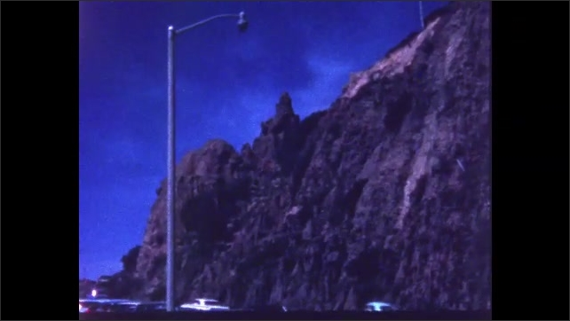 1970s: Cars parked alongside road. People walk by. Cliff above road.