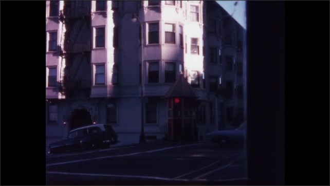 1970s: Driving down hill in San Francisco. Cars going down hill.