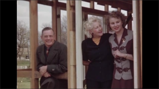 1940s ILLINOIS: Women standing in frame of building, laughing. Man and woman standing in building, laughing.