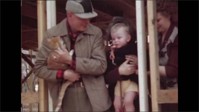 1940s ILLINOIS: Men standing in frame of building, man holds up baby on window frame. Man and woman standing in building, man holds cat, woman sets down baby with man and woman.