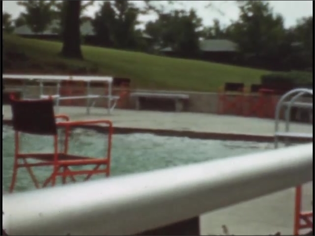 1940s: man jumping on diving board to dive into pool, Sugar Camp pool area surrounded by tables and chairs