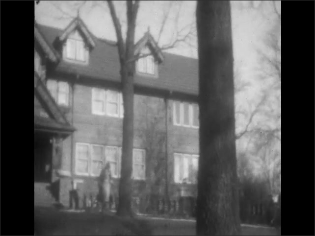 1920s: Children and woman in coats walk through fenced yard. Woman walks down sidewalk from large house in neighborhood.