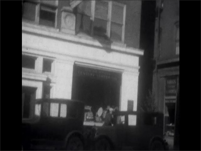 1920s: Man in coat carries bags across front lawn of home. Pedestrians walk past storefronts and parked cars in city.