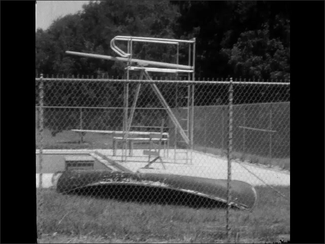 1950s: Canoe and diving board near enclosed swimming pool. Picnic buildings and grill in wooded park.