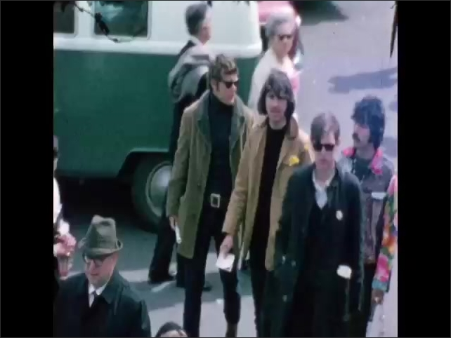 1960s: Couple in sunglasses walk down sidewalk during protest. Hippies walk past art car during protest.
