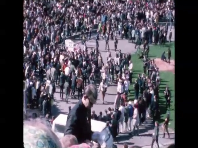 1960s: Protesters form a human chain on field. Photographers swarm around small crowd of protesters with sign on field.