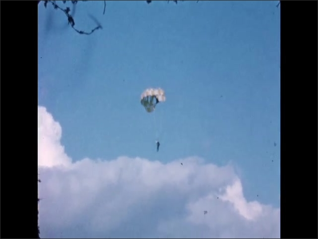 1960s: Man parachutes down through sky toward stadium. Parachutist lands in crowded stadium seating. Hippie in cape stands on bench in crowded stadium.