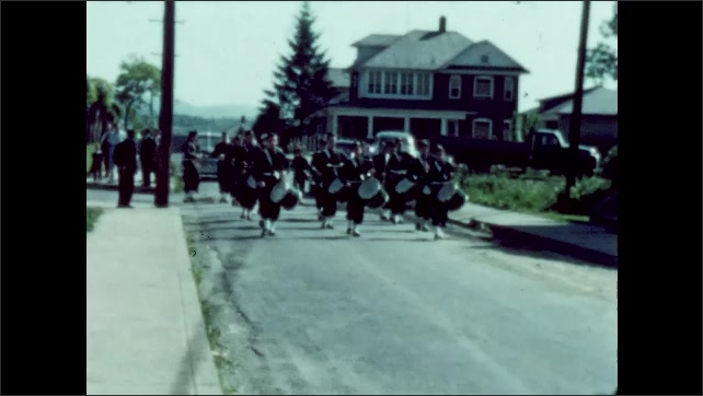 1950s: Marching band marches down street.
