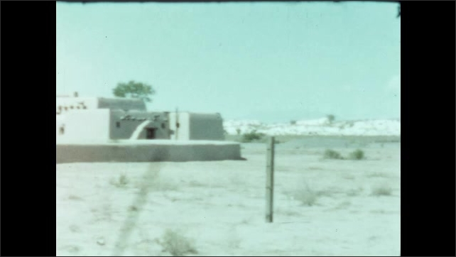 1950s: Adobe style buildings in the desert. Boy stands next to car.