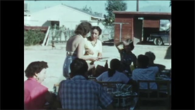 1950s: People sit outside at picnic tables. Woman carves turkey.