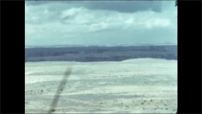 1950s: Man and little girl hold hands, walk down desert path. Desert and mountains.