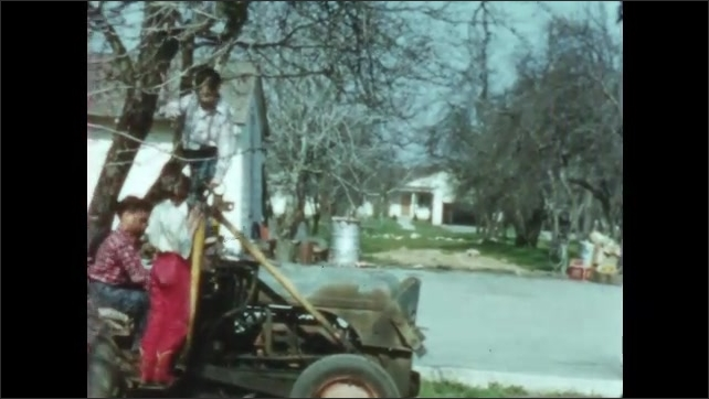1950s: Kids play on tractor and swing on tree branches. Adults watch children play.