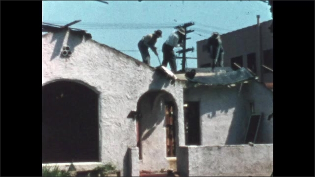 1950s: Three people dismantle roof of house. Two people taking apart roof.