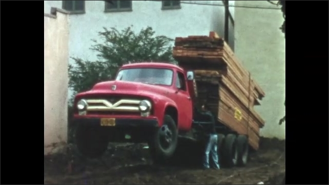 1950s: Truck with oversized load of lumber for building house, sits with front end in air. Wood on back end begins to get unloaded.