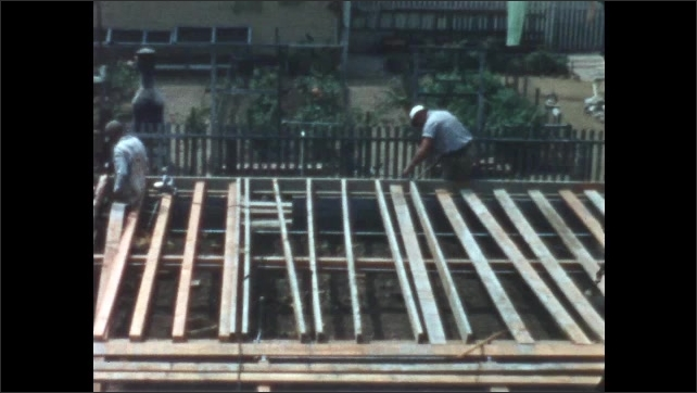 1950s: Man hammers wood on framing of foundation of building. Man hammers wood on framing of foundation. Man work on boards across floor of framing on foundation.