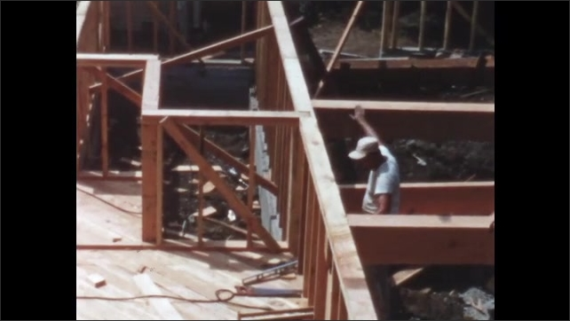 1950s: Men secure beam in place on framing of building under construction. Men lift framed wall up.