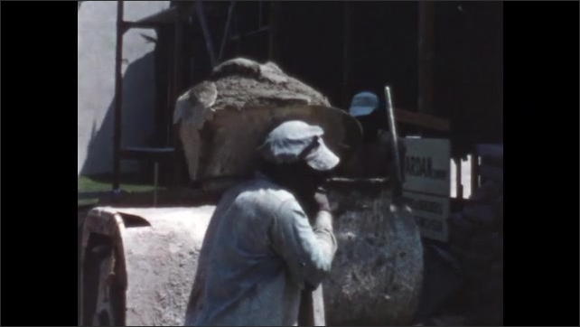1950s: Man nails up sheetrock on walls inside building under construction. Concrete stirs in mixer. Man shovel concrete onto trough and carries it over to building.