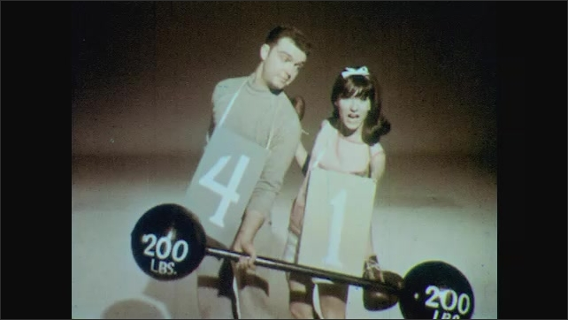1960s: Young people wear numbers and exercise.  Young man and woman pick up weight together.  People sing.  Men throw medicine ball back and forth.