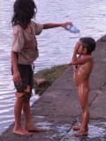 Meisje wast haar zusje, voor de tempel Angkor Wat