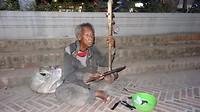 Bedelaar speelt muziek op een zefg gemaakt snaarinstrument