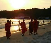 monniken op het strand bij zonsondergang