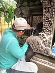 Een vakman bewerkt een steen met prachtige vormen en afbeeldingen midden in Ubud.