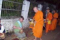 Geknield op een kleedje een hapje rijst geven aan de monniken