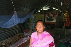 Vrouw voor haar golfplaten shelter