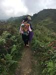 Onze gids Zizi met haar baby op de rug gaat ons voor de berg op