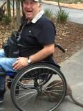 Dante/Ruben met een buidelrat onder zijn rolstoel