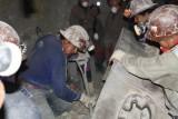 Mijners aan het werk, het overscheppen van stukken steen naar een andere kar