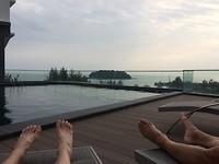 Luieren aan het zwembad met uitzicht op zee.