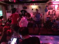 Rockband in een ruige bar, met ladyboy bediening