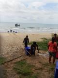 24) Kratten met vis van de boot af en kratten met eten de boot op