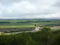Zicht op de vallei en de brede rivierbedding, nu bijna zonder water.