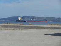 Haven Megara ,tanker wordt door sleepboot buiten de haven geloodst