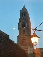 Toren van een van de kerken in Le Puy-en-Velay bij avondlicht met maneschijn