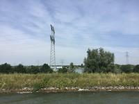 Varend in het kanaal terwijl heel laag in het dal de Maas stroomt