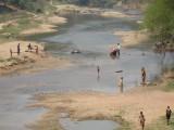 Spelende kinderen en motor schoonmaken in de rivier