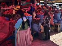 Markt in La Paz met de op de voorgrond een 'cholita' ter herkennen aan de vlechten en hoeden