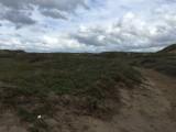 Uitgestrekte duinenlandschap met een vleugje donkere wolken