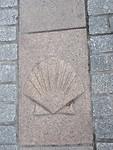 Burgos met de schelp (Pelgrimsroute naar Santiago de Compostela) in het beton op de weg