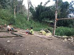 Chong, zijn baby en de buurjongen maken een nieuw wandje van bamboe